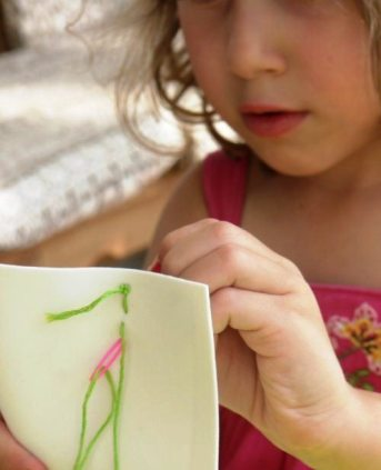 A little girl learns how to sew with plastic needles and a foam board.