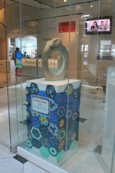 MIA front lobby podium covered in crochet hexagons to celebration of Worldwide Knit in Public Day.